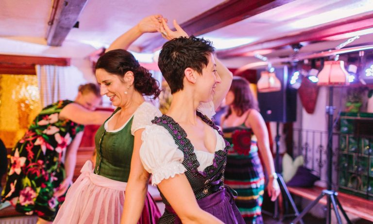 Tanzende Frauen in der Stube bekleidet mit Tracht