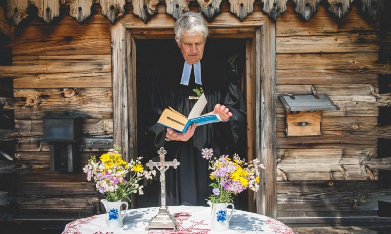 Pfarrer vor der Kapelle mit Gebetsbuch und Altar