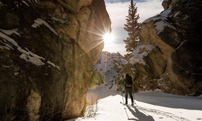 Skitourengeher durch Felsabbrüche mit Sonne