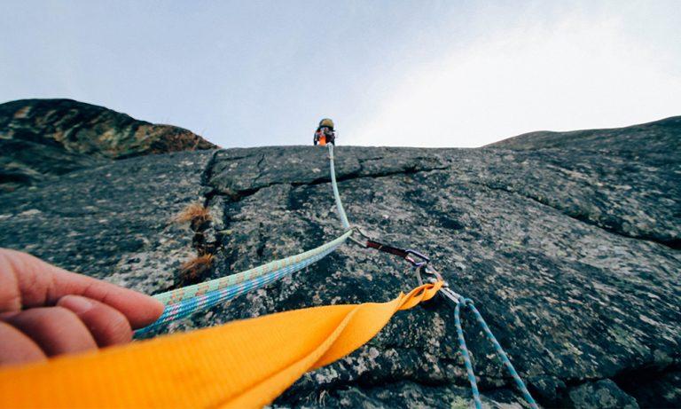 Kletterer gesichert am Seil an Felswand