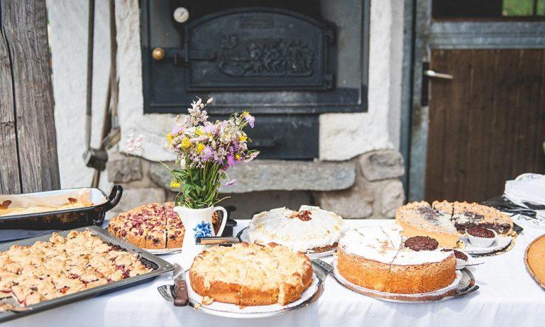 Kuchenbuffet mit Blumen vor Steinofen aufgebaut
