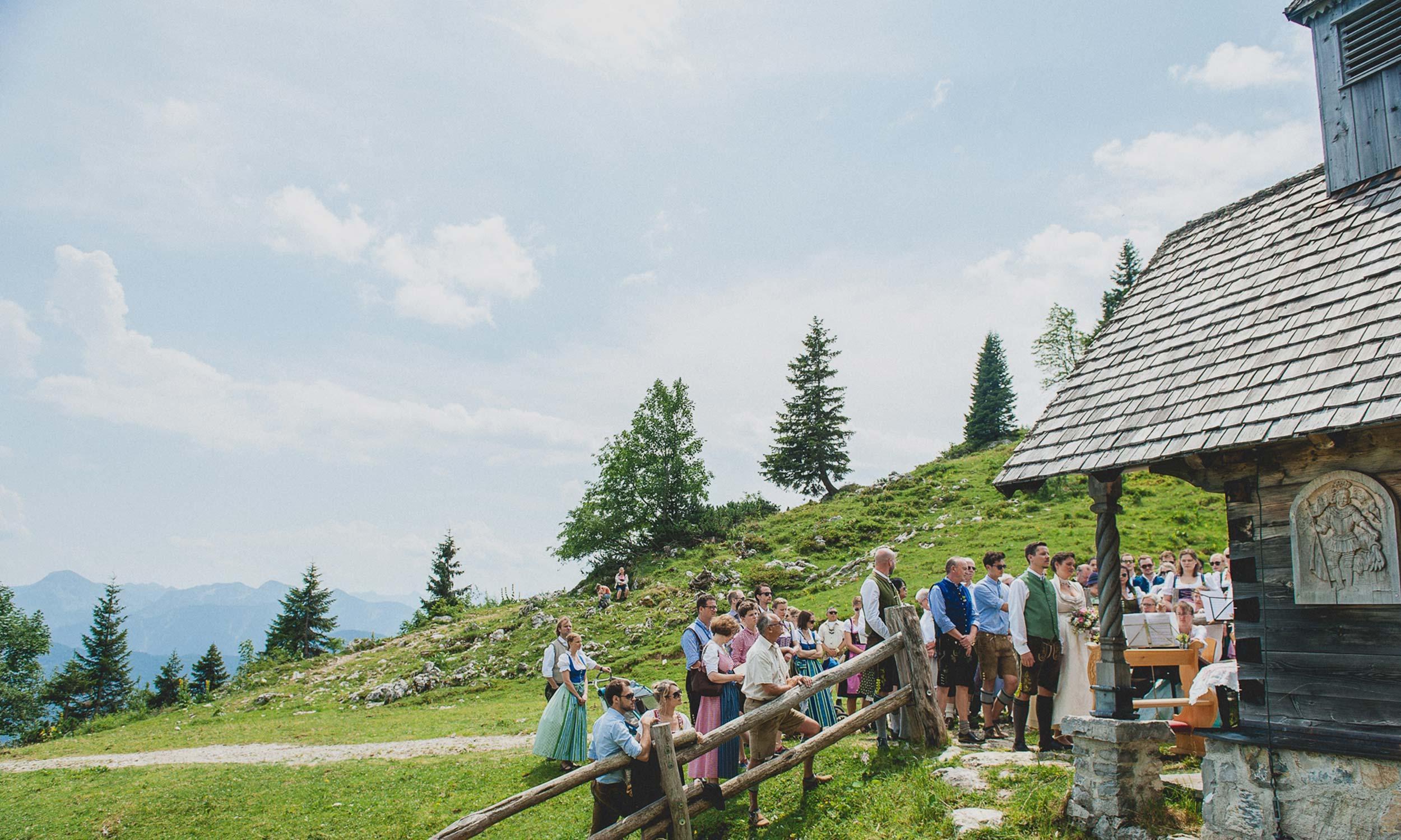 Trauung vor der Kapelle mit Brautpaar und Gaesten