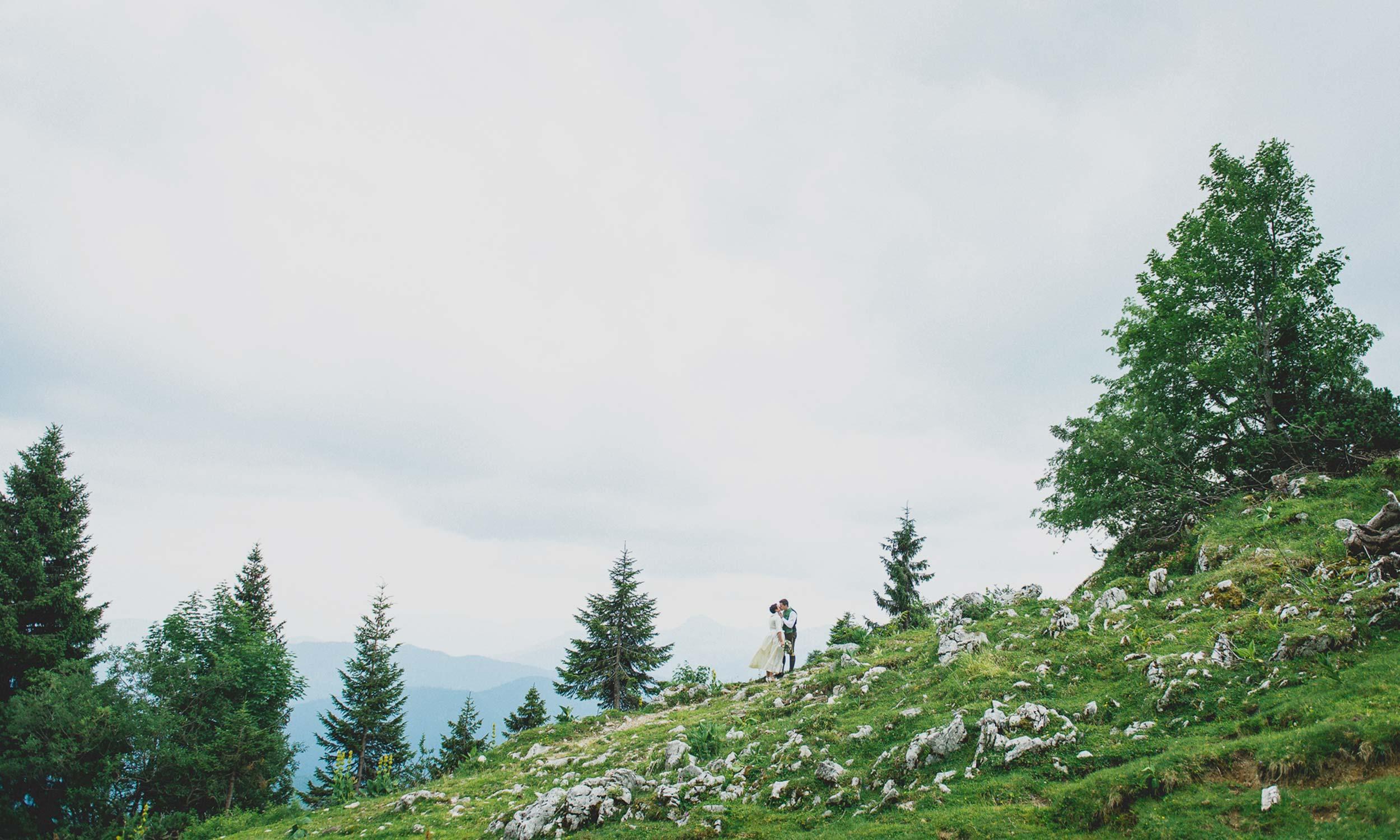 küssendes Brautpaar inmitten der Bergkulisse