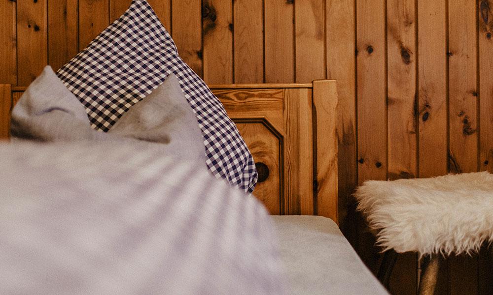 Bett im Zweibettzimmer mit Bettwäsche
