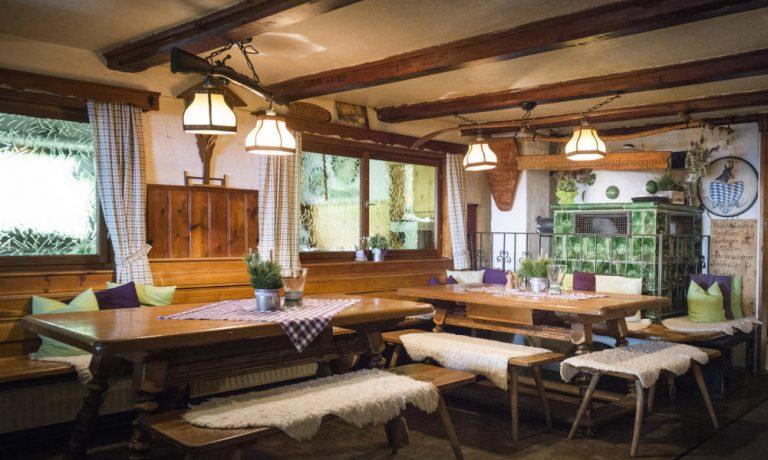 Tische in der Gaststube mit Kachelofen