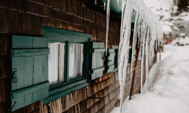 Fenster der Stiealm im Winter mit Eiszapfen vom Dach