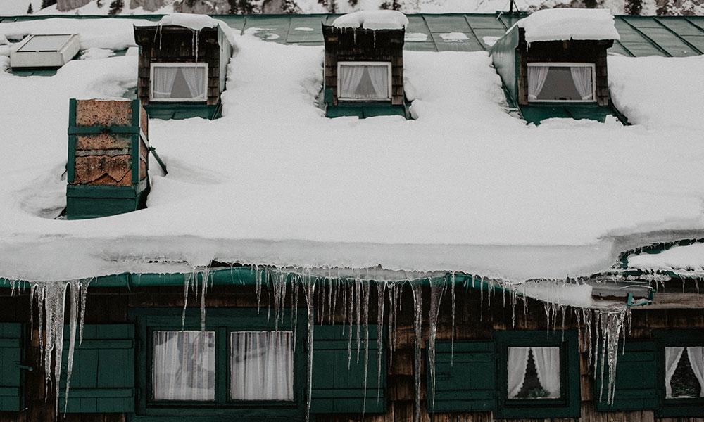 Hütte von außen mit Schnee auf dem Dach